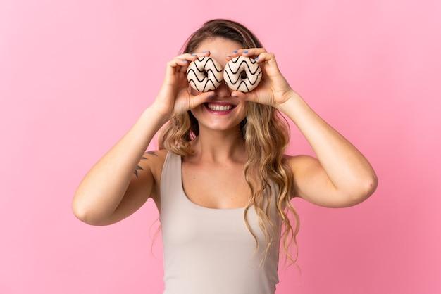 Jeune femme brésilienne isolée sur mur rose tenant des beignets dans les yeux
