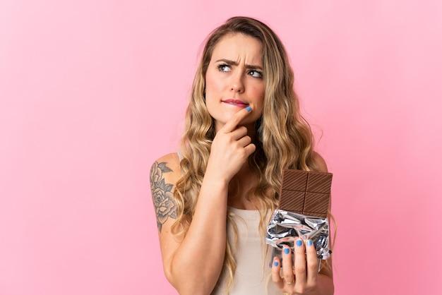 Jeune femme brésilienne isolée sur rose en prenant une tablette de chocolat et ayant des doutes