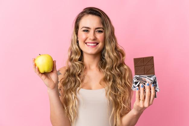 Jeune femme brésilienne isolée sur rose prenant une tablette de chocolat dans une main et une pomme dans l'autre