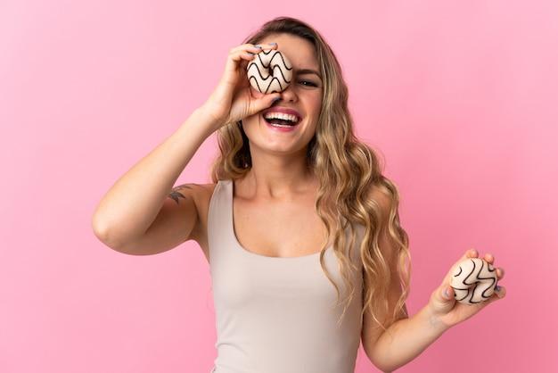 Jeune femme brésilienne isolée sur rose tenant un beignet et heureux