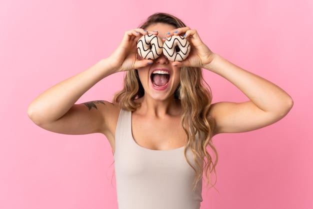 Jeune femme brésilienne isolée sur rose tenant des beignets dans un oeil