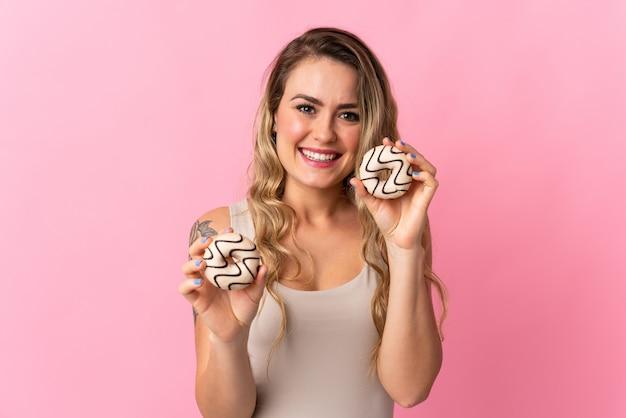 Jeune femme brésilienne isolée sur rose tenant des beignets avec une expression heureuse