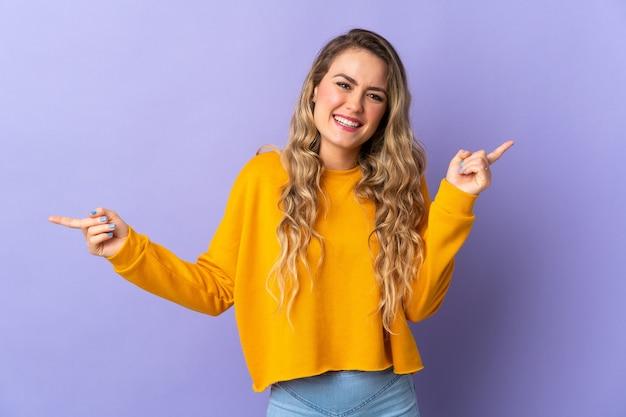 Jeune femme brésilienne isolée sur violet doigt pointé vers les côtés et heureux