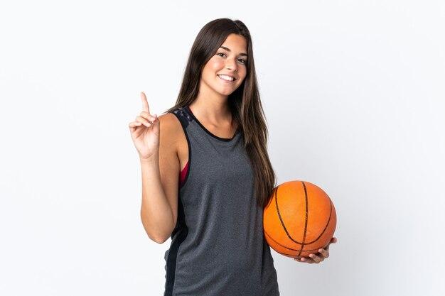 Jeune femme brésilienne jouant au basket isolé sur un mur blanc pointant vers le haut une excellente idée