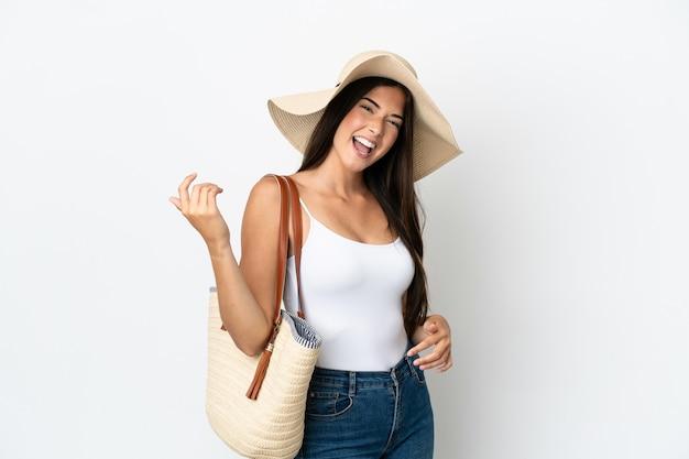 Jeune femme brésilienne avec pamela tenant un sac de plage isolé sur fond blanc faisant un geste de guitare