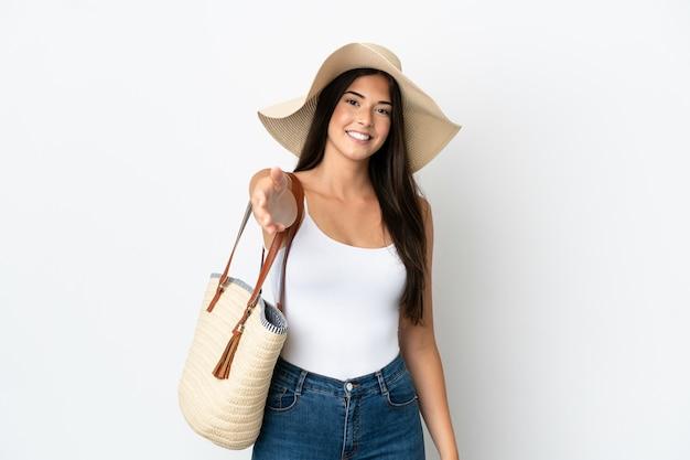 Jeune femme brésilienne avec pamela tenant un sac de plage isolé sur fond blanc se serrant la main pour conclure une bonne affaire