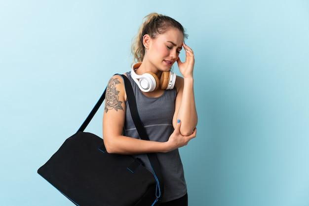 Jeune femme brésilienne sport avec sac de sport isolé sur mur bleu avec maux de tête