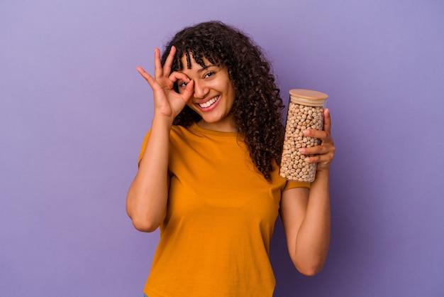 Jeune femme brésilienne tenant une bouteille de pois chiche isolée sur un mur violet excité en gardant le geste ok sur les yeux.
