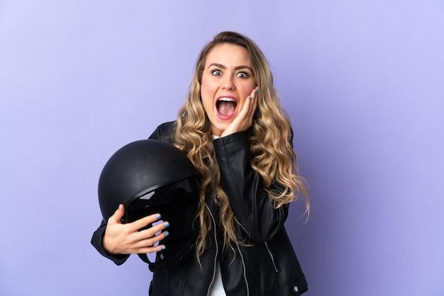 Jeune femme brésilienne tenant un casque de moto isolé sur violet avec surprise et expression du visage choqué