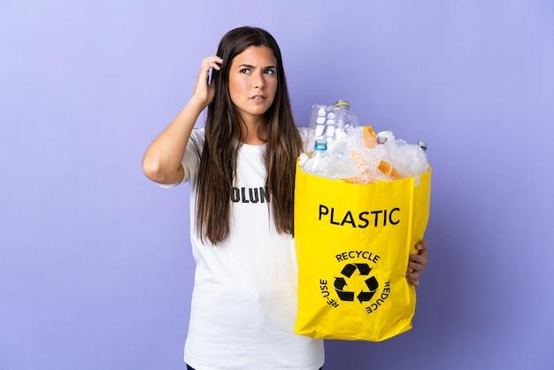 Jeune femme brésilienne tenant un sac plein de bouteilles en plastique à recycler isolé