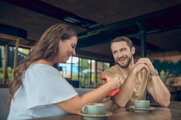 Jeune femme brillante en cadeau d'ouverture chemisier blanc et joyeux homme barbu amoureux assis dans un café d'été