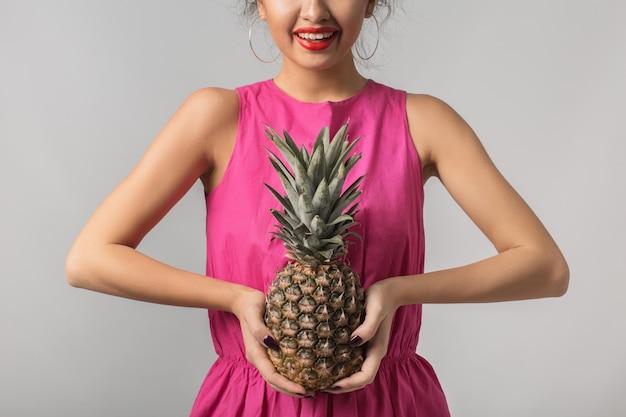 Jeune femme bronzée en chemise rose tenant ananas, émotion positive, isolé, fruits tropicaux, alimentation, sourire, lèvres rouges
