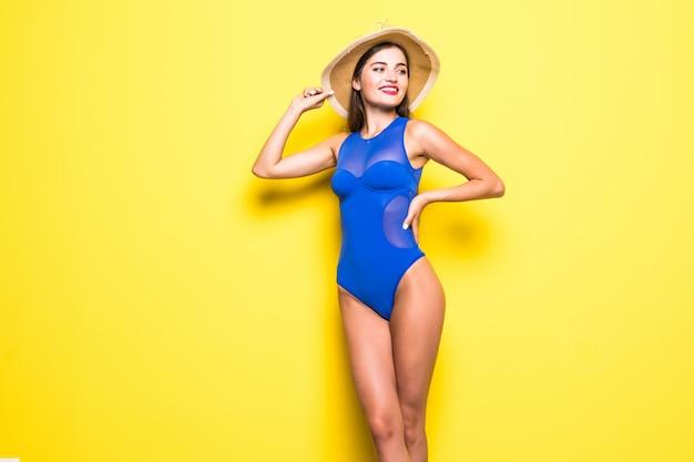 Jeune femme bronzée mince sexy en maillot de bain bleu posant contre le mur jaune. maillot de bain ou modèle de bikini