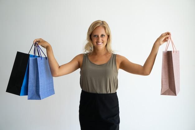 Jeune femme bronzée positive montrant des sacs à provisions et regardant la caméra.