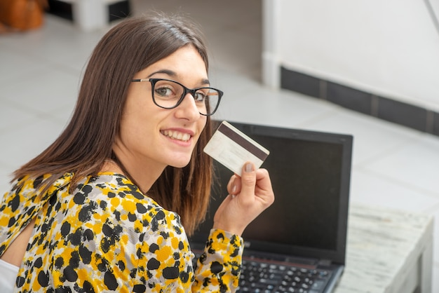 Jeune femme brune achète avec internet