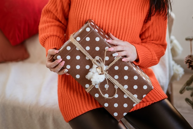 Une jeune femme brune adulte vêtue d'un pull rouge avec un cadeau joliment emballé dans ses mains est assise...
