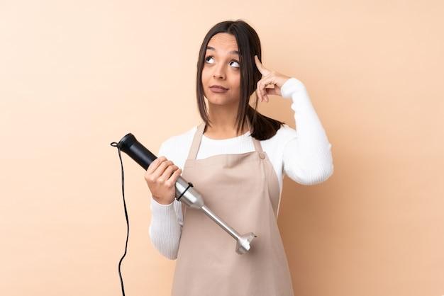 Jeune femme brune à l'aide d'un mixeur à main isolé
