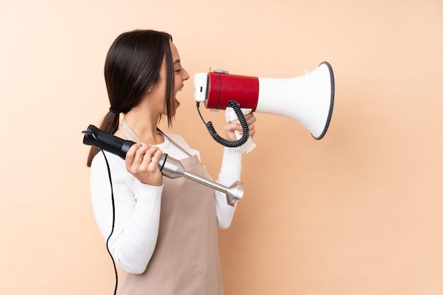 Jeune femme brune à l'aide d'un mixeur plongeant sur un mur isolé criant dans un mégaphone