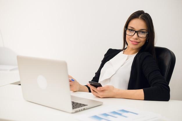Jeune femme brune à l'aide d'un téléphone au travail