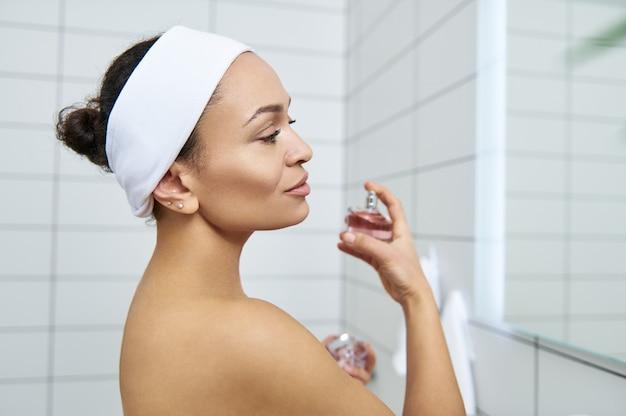 Jeune femme brune appliquant un parfum sur son cou. portrait en gros plan