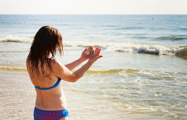 Jeune femme brune assez mince en chapeau et lunettes de soleil se bronzer sur la plage tropicale en bikini