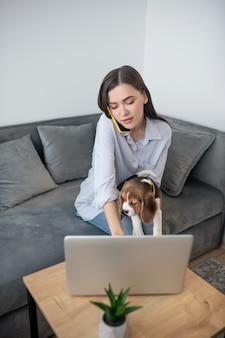 Jeune femme brune assise avec un chiot et parlant au téléphone