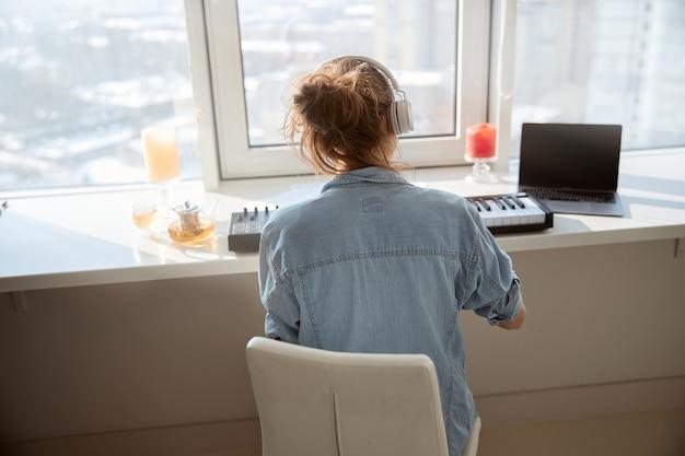 Jeune femme brune assise devant la fenêtre et penchée sur une nouvelle mélodie