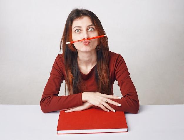 Jeune femme brune assise vêtue d'un chemisier rouge avec un livre rouge et un crayon
