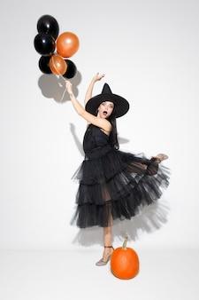 Jeune femme brune au chapeau noir et costume sur blanc