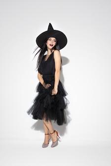 Jeune femme brune au chapeau noir et costume sur fond blanc. modèle féminin caucasien attrayant. halloween, vendredi noir, cyber lundi, ventes, concept d'automne. copyspace. danser, poser.