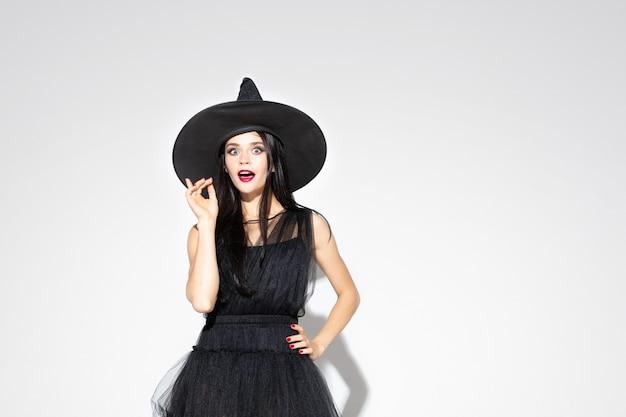 Jeune femme brune au chapeau noir et costume sur fond blanc. modèle féminin caucasien attrayant. halloween, vendredi noir, cyber lundi, ventes, concept d'automne. copyspace. pointant vers le haut.
