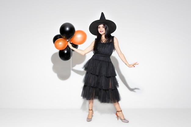 Jeune femme brune au chapeau noir et costume sur fond blanc. modèle féminin caucasien attrayant. halloween, vendredi noir, cyber lundi, ventes, concept d'automne. copyspace. tient des ballons, sourit.