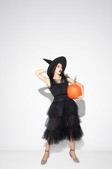 Jeune femme brune au chapeau noir et costume sur fond blanc. modèle féminin caucasien attrayant. halloween, vendredi noir, cyber lundi, ventes, concept d'automne. copyspace. tient le pompage.