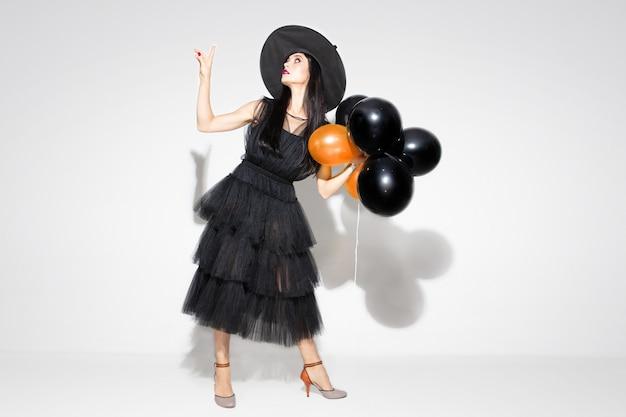 Jeune femme brune au chapeau noir et costume sur fond blanc. modèle féminin caucasien attrayant. halloween, vendredi noir, cyber lundi, ventes, concept d'automne