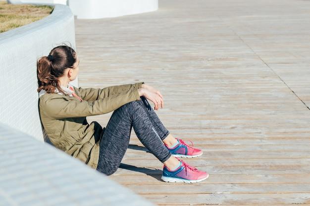 Jeune femme brune aux cheveux bouclés sportswear assis à l'extérieur et au repos après des exercices sportifs