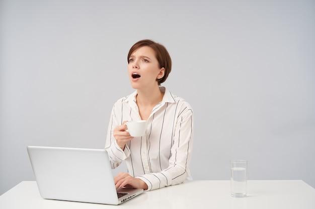 Jeune femme brune aux cheveux courts avec une coiffure décontractée criant quelque chose tout en regardant vers l'avant, gardant la main sur le clavier de l'ordinateur portable tout en ayant une tasse de thé, isolé sur blanc