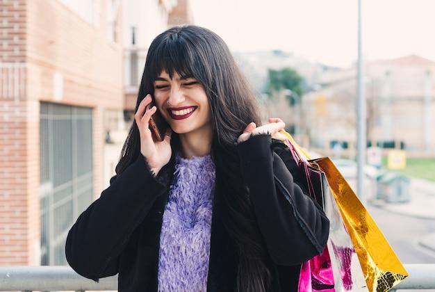Jeune femme brune aux cheveux longs et aux yeux verts faisant un appel après le shopping. sacs à provisions. lèvres peintes en grenat. concept de shopping.