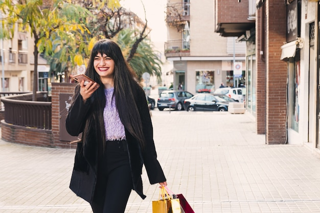 Jeune femme brune aux cheveux longs et aux yeux verts marchant avec des sacs à provisions. souriant. concept d'achat.