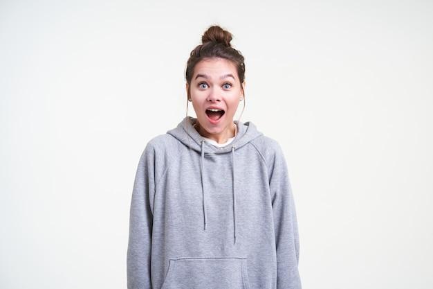 Jeune femme brune aux yeux bleus perplexe avec une coiffure décontractée chignon à la caméra avec étonnement avec de grands yeux et la bouche ouverte, isolé sur fond blanc