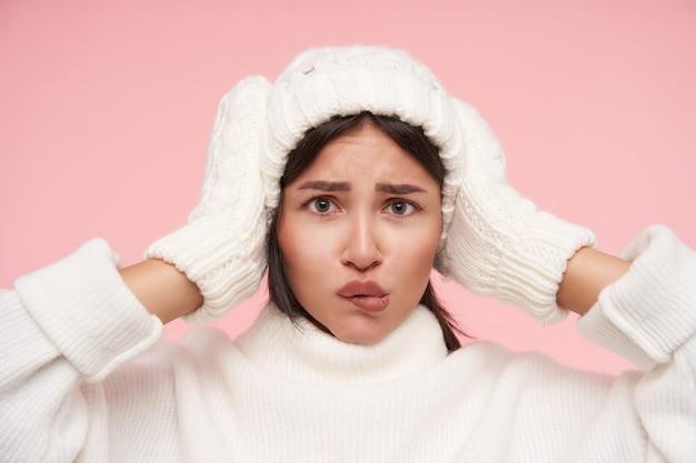 Jeune femme brune aux yeux verts perplexe avec les cheveux lâches gardant les mains levées sur sa tête tout en regardant confusément à l'avant, debout sur le mur rose