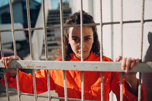 Jeune femme brune bouclée en costume orange. portrait de femme en salopette colorée.