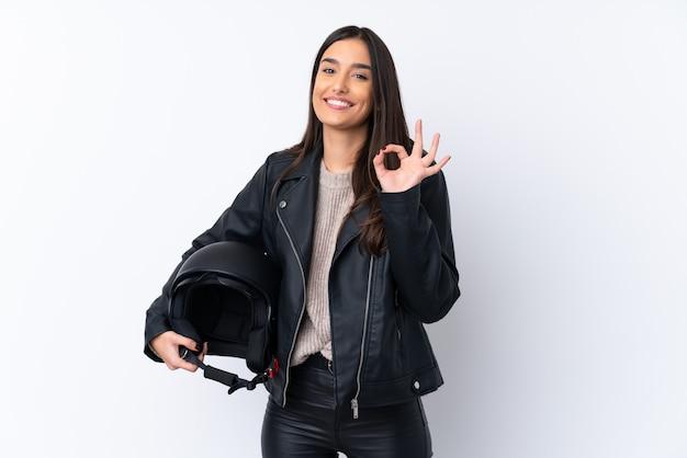 Jeune femme brune avec un casque de moto sur blanc montrant signe ok avec les doigts