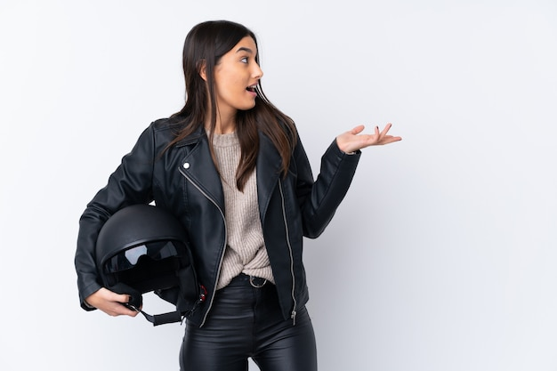 Jeune femme brune avec un casque de moto sur un mur blanc isolé avec une expression faciale surprise