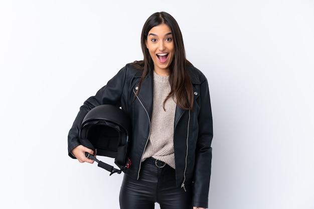 Jeune femme brune avec un casque de moto sur un mur blanc isolé avec surprise et expression faciale choquée
