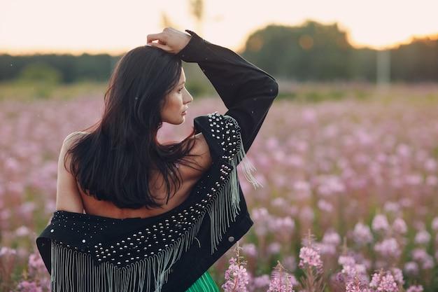 Jeune femme brune sur le champ de fleurs sally en fleurs. fleurs et fille lilas.