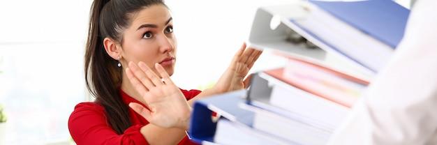 Jeune femme brune en chemise rouge assis dans le bureau et refusant de travailler avec des tas de documents.