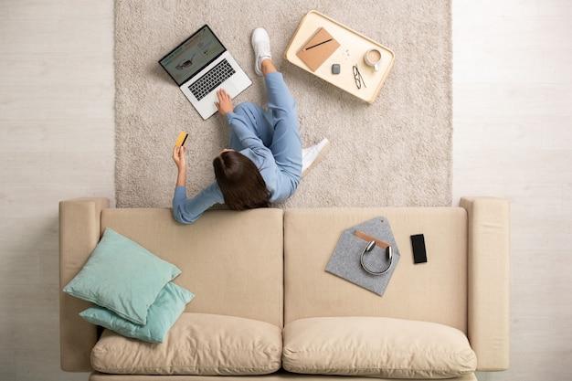 Jeune femme brune contemporaine en pyjama bleu reposant sur le sol par canapé pendant les achats en ligne à loisir dans un environnement domestique