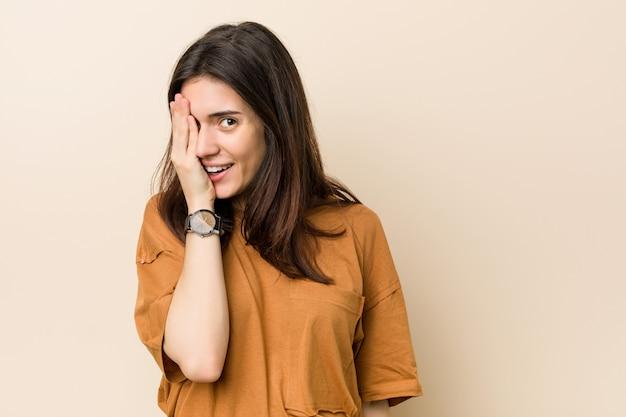 Jeune femme brune contre un beige s'amuser couvrant la moitié du visage avec palme.