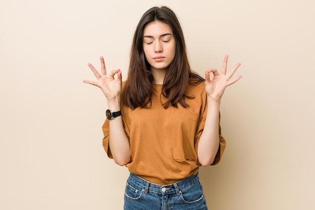 Jeune femme brune contre un beige se détend après une dure journée de travail, elle pratique le yoga.