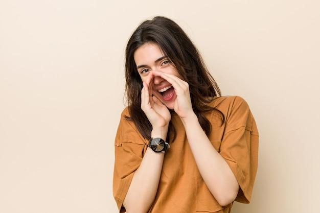 Jeune femme brune contre un fond beige criant excité à l'avant.